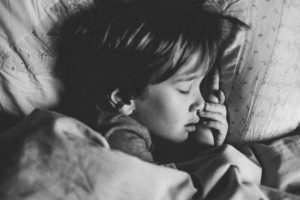 child in bed with ear infection