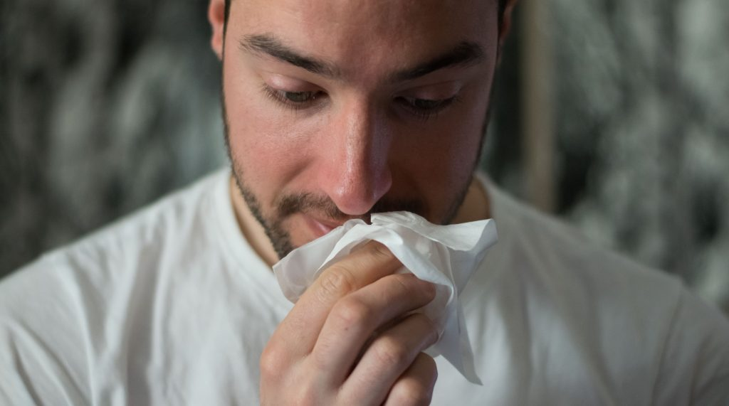 man with seasonal allergies holding tissue